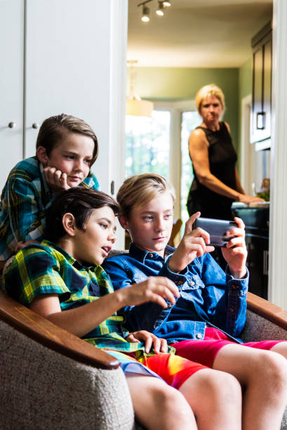 mother with a real look of displeasure on her face watching boys using the internet on a phone - mom spying stock photos and pictures