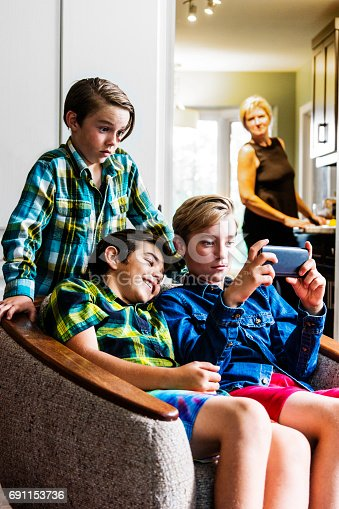 A mother looks on from the kitchen as pre-teen boys use a smartphone in the living room.  She is out of focus but it is clear to see an approving smile on her face.