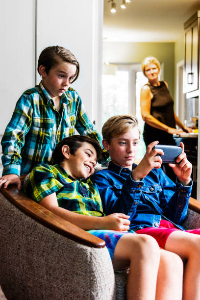 mother with a slight smile look on her face watching boys using the internet on a phone - mom spying stock photos and pictures