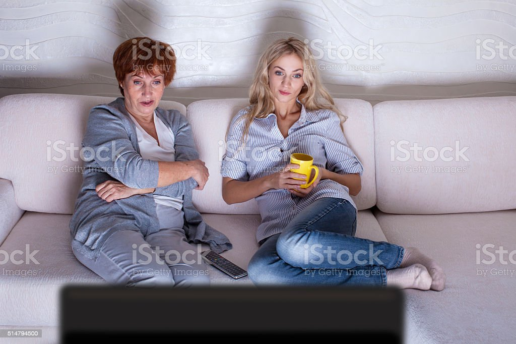 Mother with adult daughter watching television stock photo