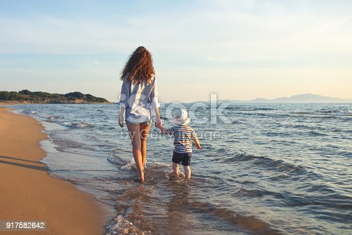 istock Mother with baby are walking at the beach 917582642