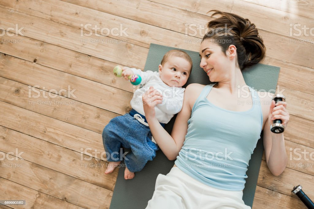 Top view of mother with baby boy lying on floor and playing with...