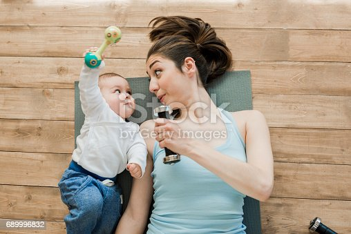 istock mother with baby boy lying on floor and playing with dumbbells 689996832