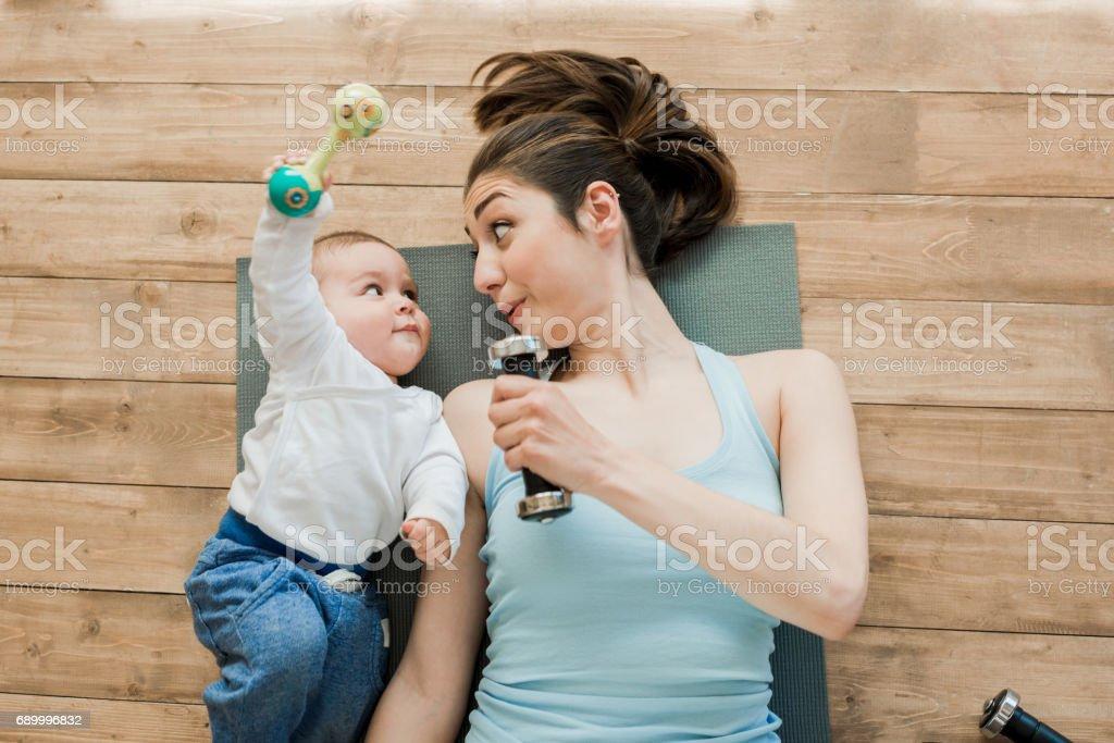 Mutter mit Baby am Boden liegen und spielen mit Hanteln – Foto