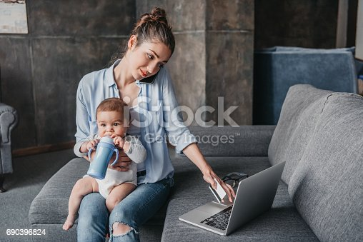 istock mother with baby boy remote working and using laptop 690396824