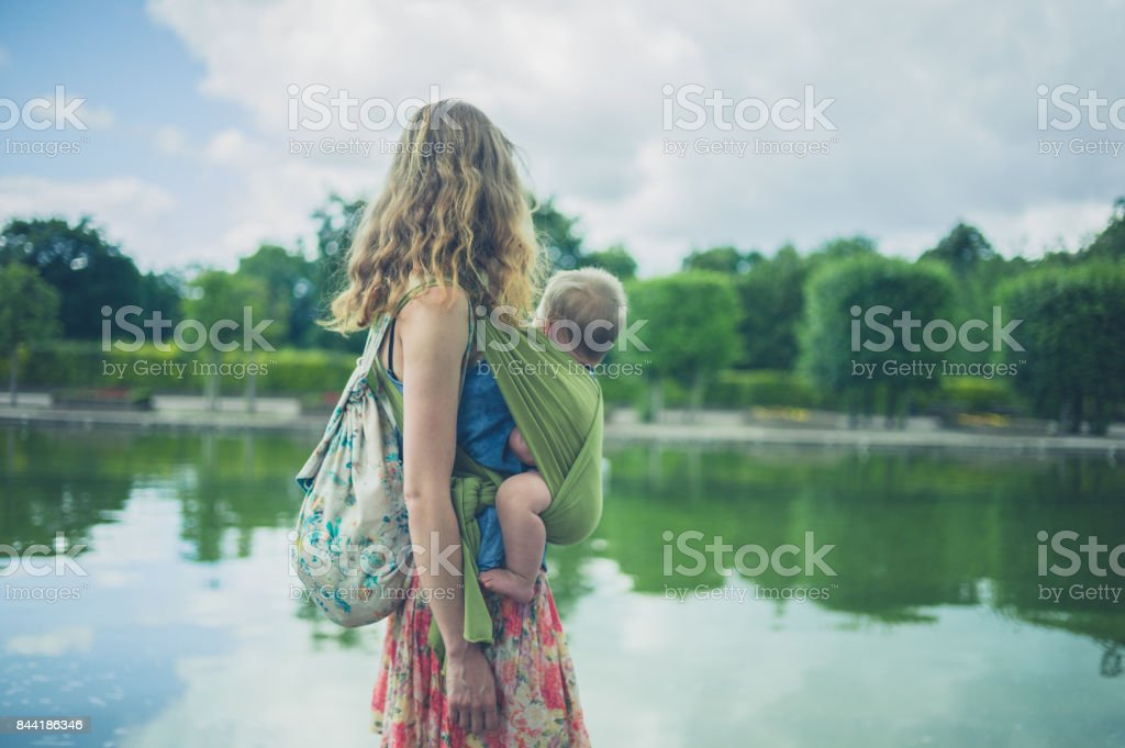 Mother with baby in sling by pond in park stock photo
