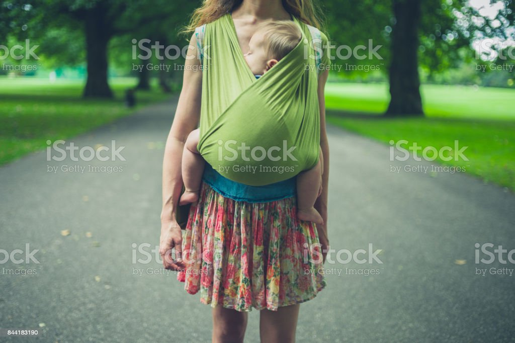 Mother with baby in sling walking in park stock photo