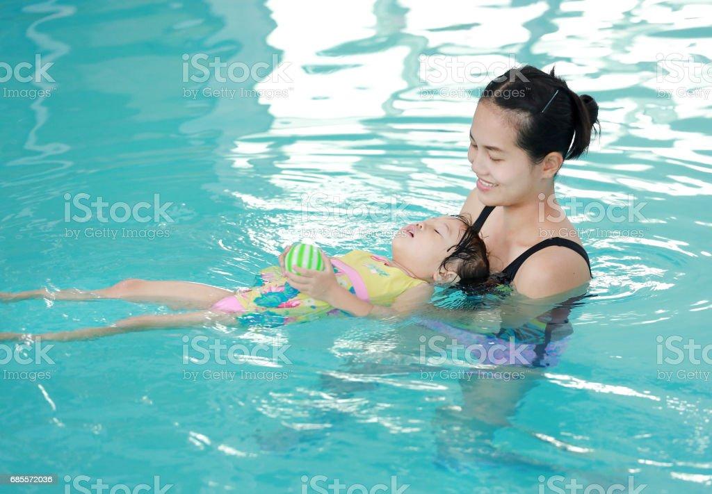 母親抱著嬰兒游泳池訓練。 免版稅 stock photo