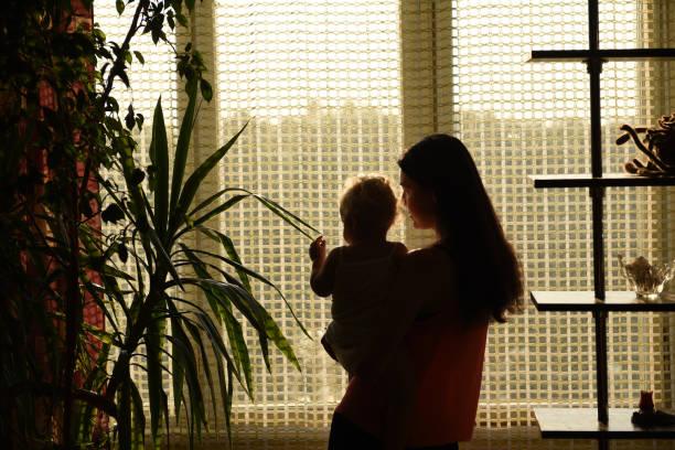 Mère avec le bébé regardant par la fenêtre. - Photo