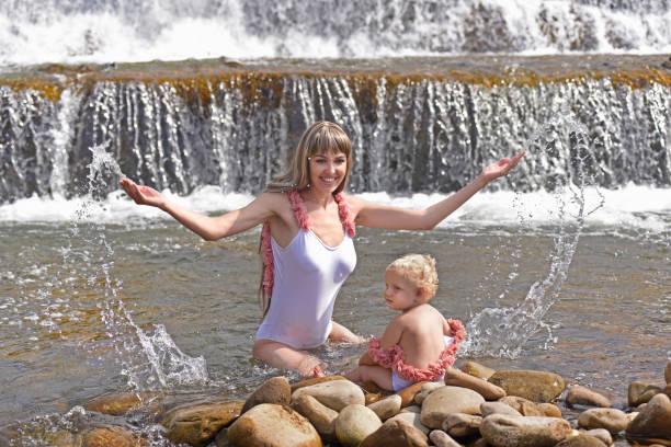 Mère avec le bébé près de la chute d'eau. - Photo