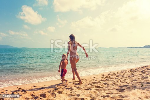 istock Mother with baby runnig at tropical beach 544586628