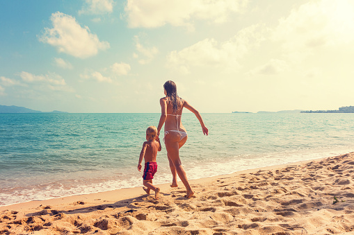 Mother with baby runnig at tropical beach