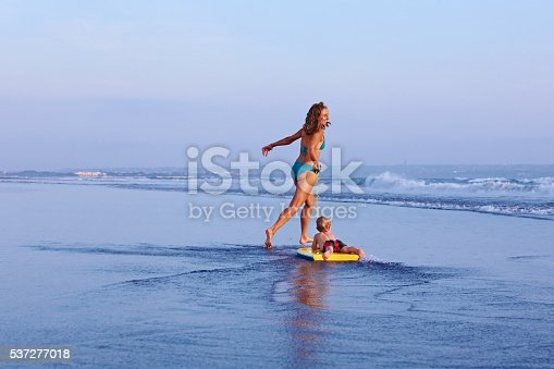 583830686istockphoto Mother with baby son on surfing board run along beach 537277018