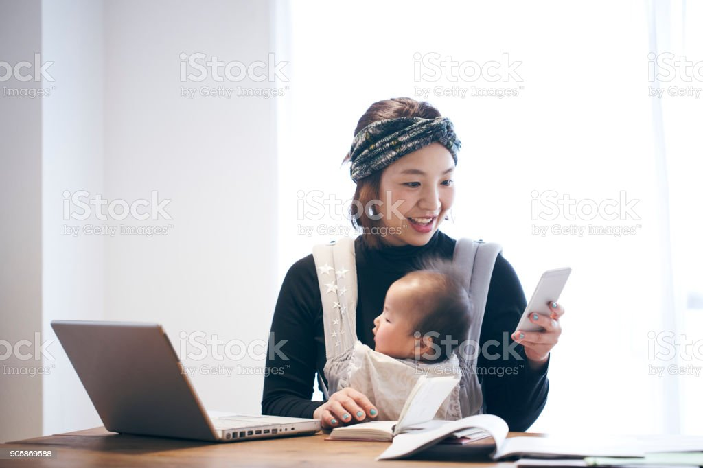 Mother with baby working at home stock photo