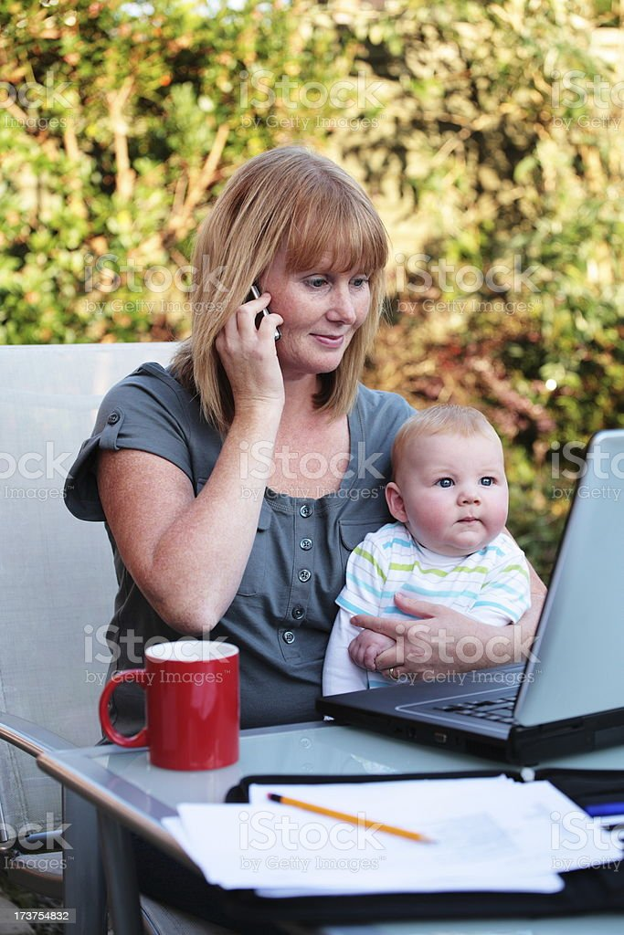 Mother with Baby Works on Laptop royalty-free stock photo