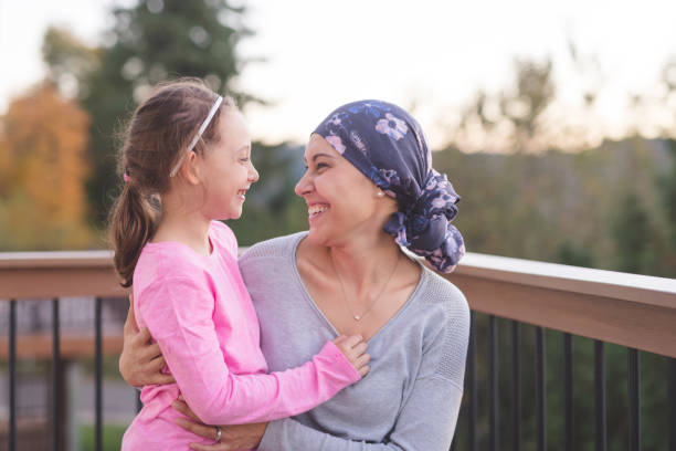 Mother with Cancer Hugging Daughter A young mother fighting cancer and wearing a head scarf hugs her daughter and smiles at her deeply as they share a few moments of tranquility together outdoors on a deck. cancer cell stock pictures, royalty-free photos & images
