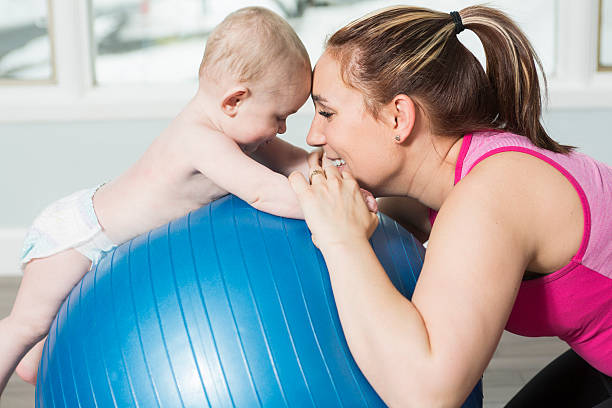 Mother with child boy doing fitness exercises stock photo