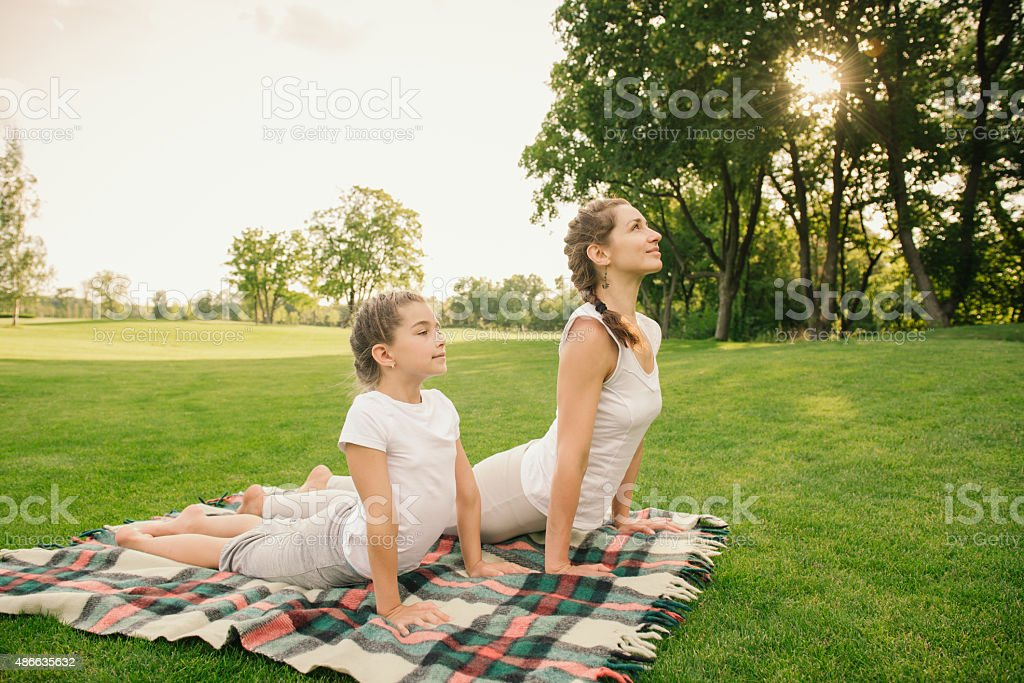Mother with child doing yoga exercise stock photo