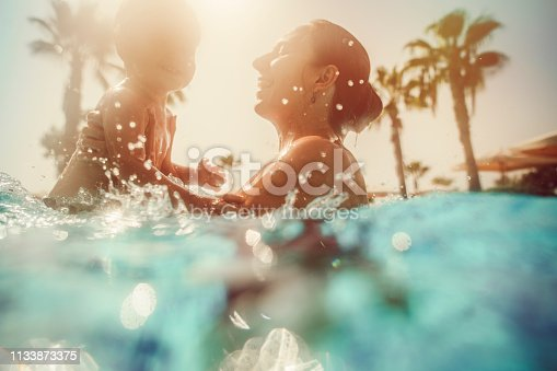 istock Mother with child having fun in pool at sunset 1133873375