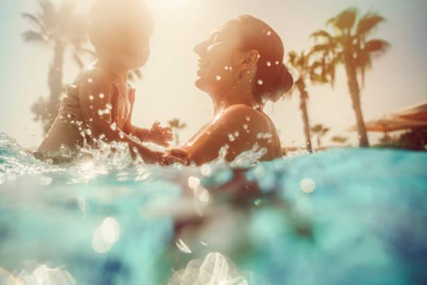 mutter mit kind, die bei sonnenuntergang spaß im pool hat - hotels in der türkei stock-fotos und bilder