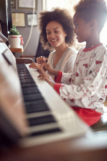 mother with child on Christmas play music on piano. concept of holidays and family happiness. stock photo
