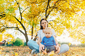 Mother walking with child in park in autumn