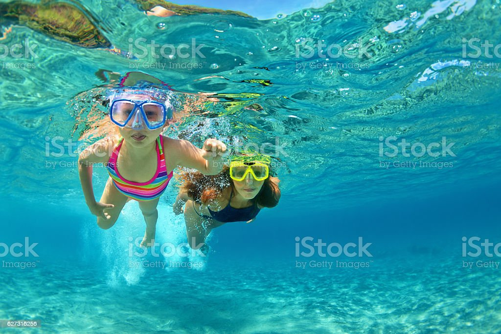 Mother with child swim underwater with fun in sea stock photo