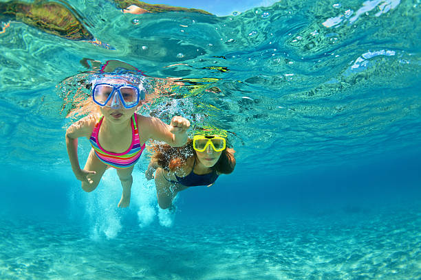 Mother with child swim underwater with fun in sea Happy family - mother with baby girl dive underwater with fun in sea pool. Healthy lifestyle, active parent, people water sport outdoor adventure, swimming lessons on beach summer holidays with child snorkel stock pictures, royalty-free photos & images