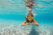 Happy active family - mother, baby son snorkel and dive together underwater in sea pool. Healthy people lifestyle, water sport outdoor adventure, swimming lesson on summer beach vacation with child
