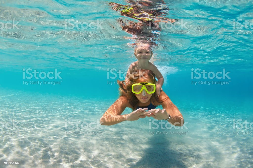 Mother with child swim underwater with fun in sea - foto stock