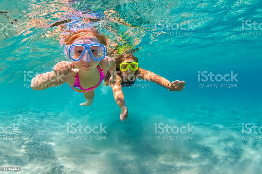Mother with child swim underwater with fun in sea Happy family - mother with baby girl dive underwater with fun in sea pool. Healthy lifestyle, active parent, people water sport outdoor adventure, swimming lessons on beach summer holidays with child 4-5 Years Stock Photo