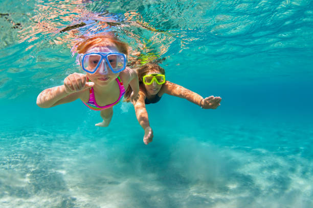 mother with child swim underwater with fun in sea - underwater diving stock photos and pictures