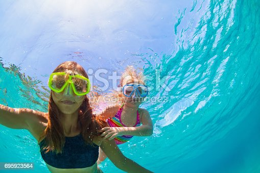 istock Mother with child swim underwater with fun in sea 695923564