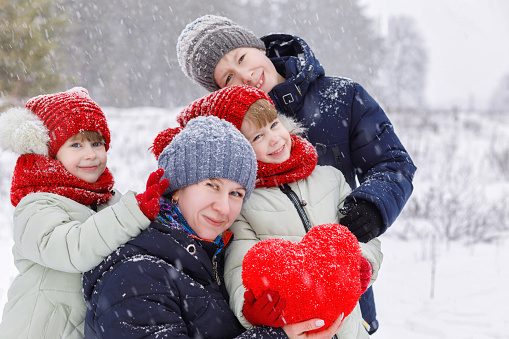 A mother with her daughters twins and her son dressed in warm colorful clothes are playing outdoors in winter park with huge heart in their hands. The concept is family St. Valentine day celebration .