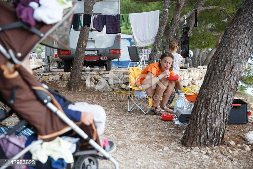 Mother with children at the campsite, preparing food in camp kitchen, checking on sleeping baby in a stroller. Active natural lifestyle, family time, home away from home concept.