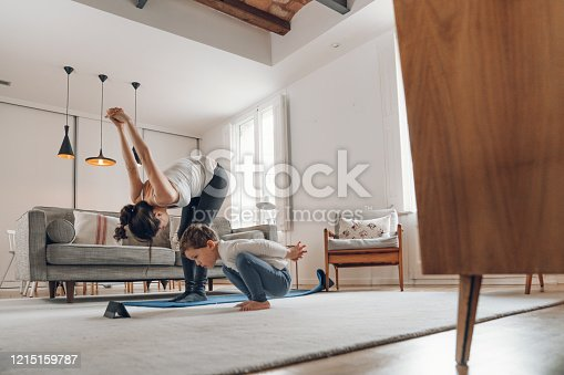 istock Mother with children doing Yoga at home 1215159787