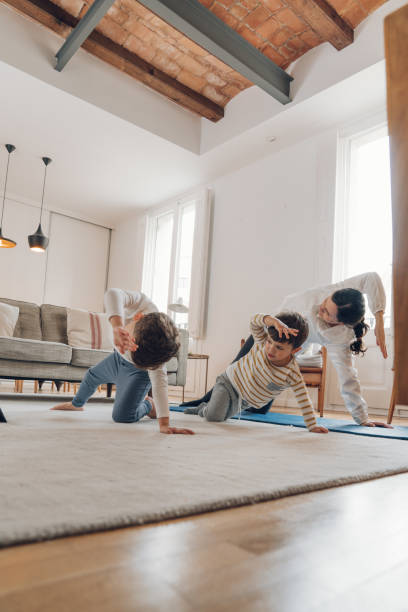 Mother with children doing Yoga at home stock photo