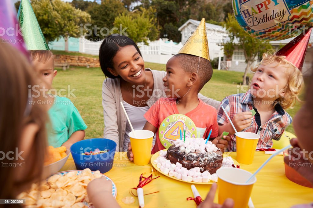 Mother With Children Enjoying Outdoor Birthday Party Together stock photo