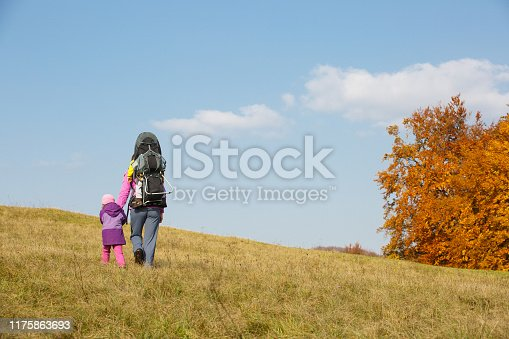 istock Mother with children hiking on a nice autumn day carrying kid 1175863693