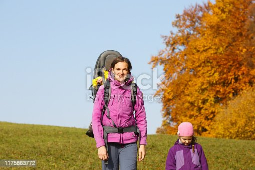 istock Mother with children hiking on a nice autumn day carrying kid 1175863772