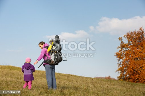 istock Mother with children hiking on a nice autumn day carrying kid 1175864078