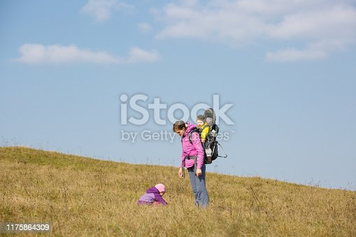 istock Mother with children hiking on a nice autumn day carrying kid 1175864309