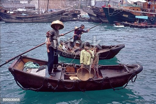 Hong Kong, China, 1974. Two women rowing with their children on two small boats in the harbor of Hong Kong.