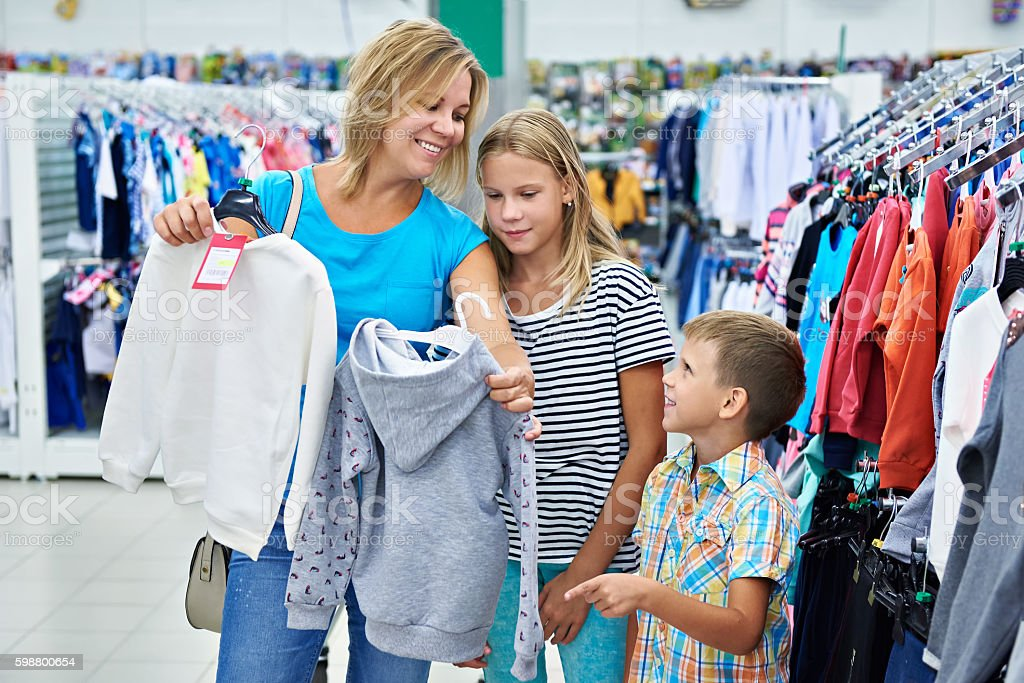 Mother with children in clothing store stock photo