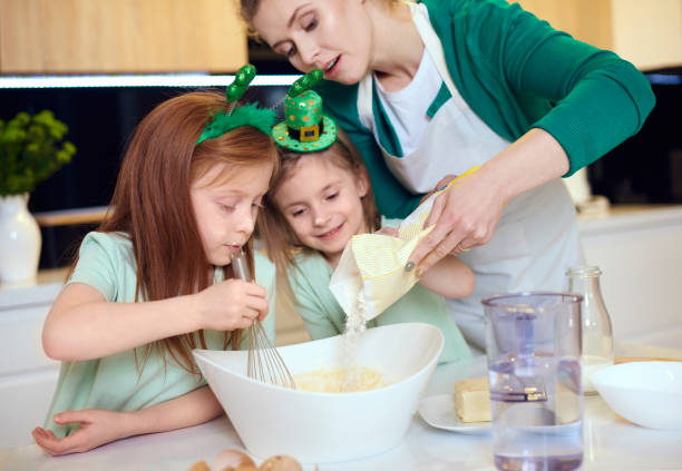 mother with children making cookies - st patricks day food stock photos and pictures