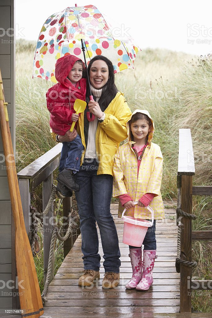 Mother with children on rainy beach royalty-free stock photo