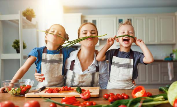 madre con bambini che preparano insalata di verdure - cucinare foto e immagini stock