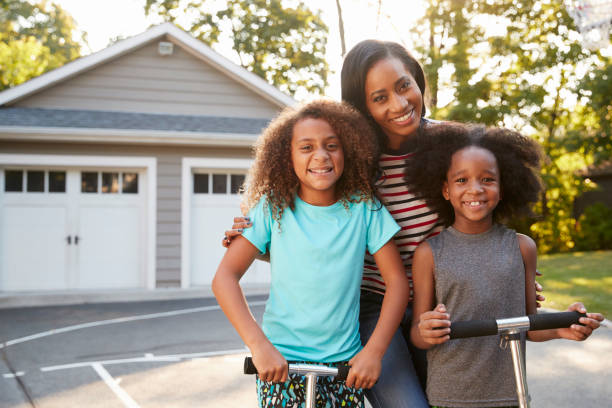 Mother With Children Riding Scooters On Driveway At Home stock photo