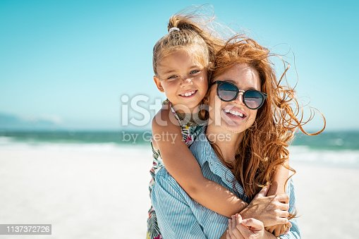 Smiling mother and beautiful daughter having fun on the beach. Portrait of happy woman giving a piggyback ride to cute little girl with copy space. Portrait of happy blonde kid embracing her mom wearing spectacles at beach during summer vacation.