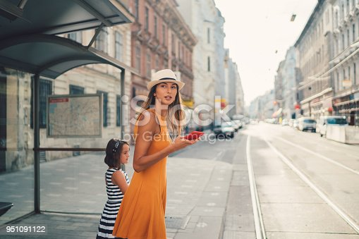 Mother with daughter at the street waiting for a bus or taxi
